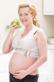 Pregnant woman eating apple royalty free stock photos
