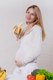 Pregnant woman eating a banana Royalty Free Stock Photography