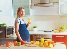Pregnant woman eating banana Stock Image