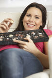 Pregnant Woman Eating Box Of Chocolates Sitting On Sofa At Home Royalty Free Stock Photography