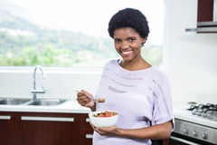 Pregnant woman eating cereal. In kitchen Stock Photos