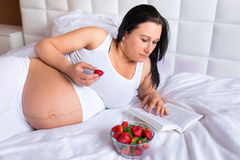 Pregnant woman eating fresh strawberries. In bed Royalty Free Stock Photo