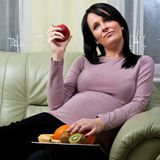 Pregnant woman eating fruit Royalty Free Stock Photography