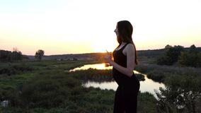 Pregnant woman eating green apple near lake at sunset. Beautiful action in the real time stock footage