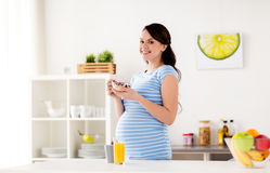 Pregnant woman eating muesli for breakfast at home Stock Photography