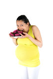 Pregnant woman eating muffins Stock Photography