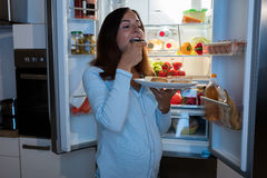 Pregnant Woman Eating Pickle In Kitchen. Young Pregnant Woman Enjoy Eating Jar Of Pickle In Front Of Refrigerator In Kitchen Royalty Free Stock Photo