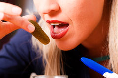 Pregnant woman eating pickles Stock Photo