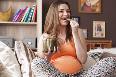 Pregnant woman eating pickles Stock Photos