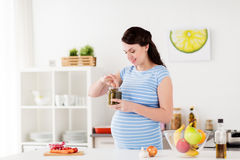 Pregnant woman eating pickles at home kitchen Royalty Free Stock Image