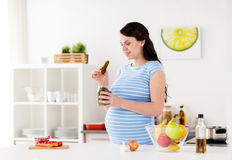 Pregnant woman eating pickles at home kitchen Stock Photography
