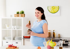 Pregnant woman eating pickles at home kitchen. Pregnancy, nutrition and people concept - happy pregnant woman eating pickles at home kitchen Stock Photos