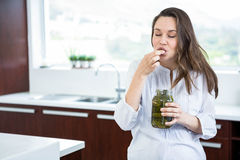 Pregnant woman eating pickles Royalty Free Stock Image