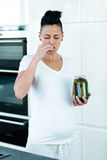 Pregnant woman eating pickles Stock Image