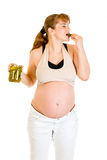 Pregnant woman eating pickles with relish Stock Photography