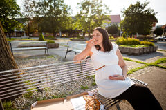 Pregnant woman eating pizza slice. Urban shot. Royalty Free Stock Images
