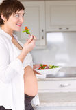 Pregnant woman eating a salad Stock Images