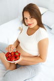 Pregnant Woman Eating Strawberry at home. Healthy Food Concept. Royalty Free Stock Images