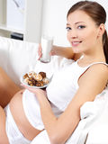 Pregnant woman eating sweet cookies with milk Royalty Free Stock Image