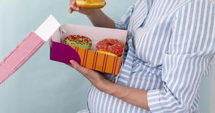 Pregnant woman eating tasty donuts while sitting. Pregnant woman opens a box of buns and eats tasty donuts while sitting. Enjoying food being pregnant on a blue stock video footage