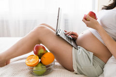 Pregnant woman eats apple while chatting in laptop. Work and relax combining, fresh fruits and healthcare concept of special mother-to-be period stock photo