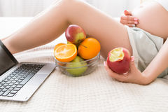 Pregnant woman eats apple and takes a break Royalty Free Stock Photography
