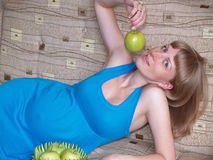 The pregnant woman eats green apple, lying on a sofa.  Stock Photo