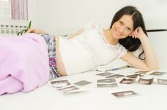 Pregnant woman enjoy looking at ultrasound scan of baby Royalty Free Stock Photography