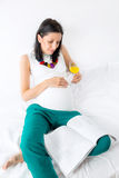 Pregnant Woman Enjoying A Morning Glass Of Orange Juice In Bed Stock Photo