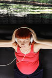 Pregnant woman enjoying music overhead Royalty Free Stock Images