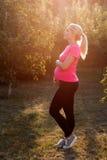 Pregnant woman enjoying sunrise at garden stock image