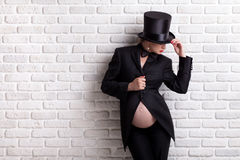 Pregnant woman in evening dress and hat cylinder. Stock Photos