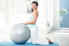Pregnant woman with exercise ball kneeing on mat Royalty Free Stock Photos