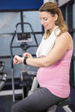 Pregnant woman on exercise bike using smartwatch. At the gym Royalty Free Stock Photo