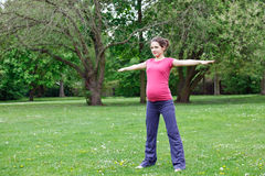 Pregnant woman exercising. In the park Stock Photography