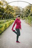 Pregnant woman exercising in autumn outdoor. Fitness pregnant woman stretching legs and exercising outdoor at urban park on early autumn. Gravid female athlete Stock Photography