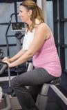Pregnant woman on exercising bike Stock Photos