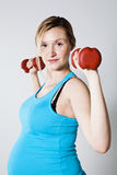 Pregnant woman exercising with dumbbells Royalty Free Stock Images