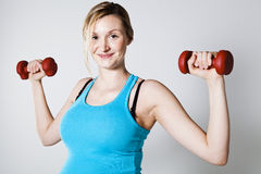 Pregnant woman exercising with dumbbells Stock Photography