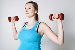 Pregnant woman exercising with dumbbells Royalty Free Stock Photography