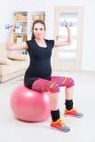 Pregnant woman exercising at home Stock Photos