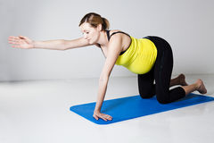 Pregnant woman exercising on mat Stock Images