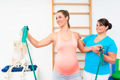 Pregnant woman exercising with resistance band in physiotherapy. Pregnant women exercising with resistance band in physiotherapy with personal trainer Royalty Free Stock Photography