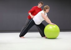 Pregnant woman exercising with trainer Royalty Free Stock Image