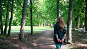 Pregnant woman expectant mother walking through park tree alley stock video