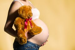 Pregnant woman, expectant mother on yellow background, close-up of pregnant belly. Activity during pregnancy royalty free stock photo