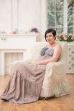 Pregnant woman expecting her baby. Full-length portrait of beautiful dark-haired smiling pregnant woman wearing great long dress sitting in the very comfortable Royalty Free Stock Photography