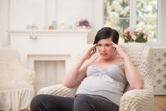 Pregnant woman expecting her baby. Selected focus on dark-haired anxious pregnant woman wearing nice shirt and black pants thinking about something very Royalty Free Stock Image