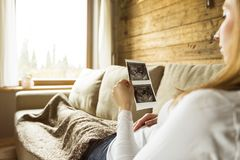 Pregnant woman expecting newborn and holding ultrasound while lying comfortably on couch stock images