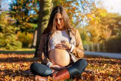 Pregnant woman sits in the park and enjoys the autumn sunshine royalty free stock photo